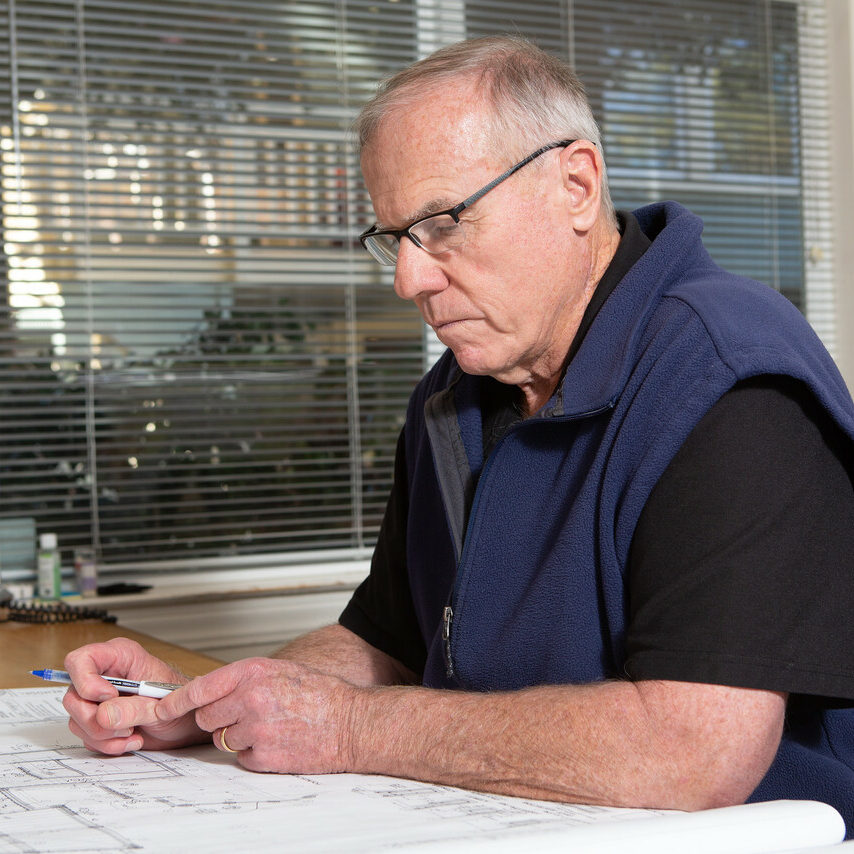Brian Gannon – Founder + Project Manager, Gannon Construction Company at his desk with plans